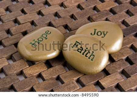 "Gold inspiration stones.  Etched with the words ""Hope"", ""Faith:, and ""Joy"". - stock photo"