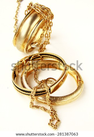 gold jewelry, bracelets and chains on a white background - stock photo