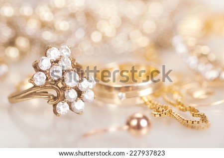 Gold jewelry with diamonds with reflection. - stock photo