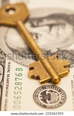gold key on hundred dollar bill - stock photo