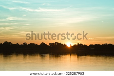Gold light on sun set with light on the river.Idyllic Wallpaper Setting Sun. - stock photo