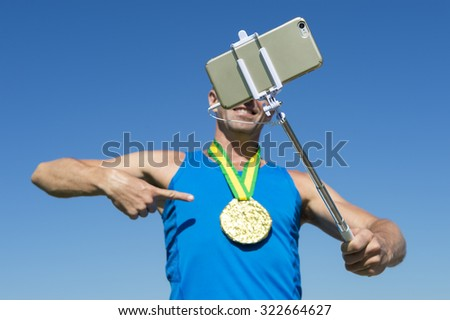 Gold medal athlete smiling for a selfie with a mobile phone on a selfie stick - stock photo