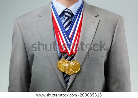 Gold medals hanging around a businessman neck concept for success and winning in business - stock photo