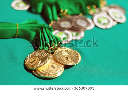 Gold medals of winners on a green background. Gold medals of prize-winners. First place. - stock photo