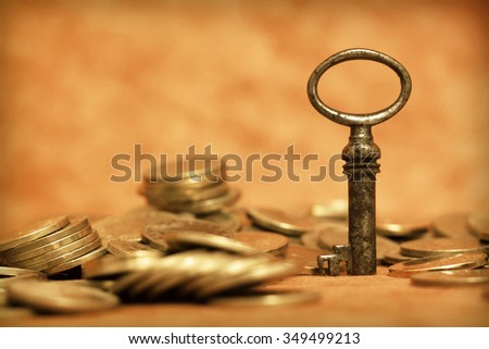 Gold money coins with an antique key - stock photo