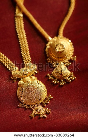 Gold Necklaces on textured cloth background. - stock photo