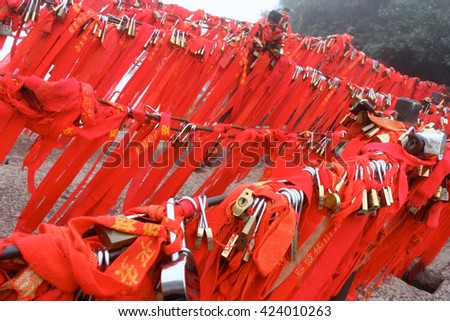 Gold padlocks and red ribbons at Gold Lock pass on Mount Hua or Hua shin, near Huayin in Shaanxi province. One of the Five Great Mountains of China, and has a long history of religious significance. - stock photo
