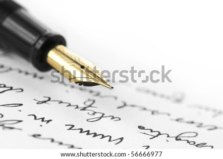Gold pen with hand written letter. Focus on end tip of fountain pen. - stock photo