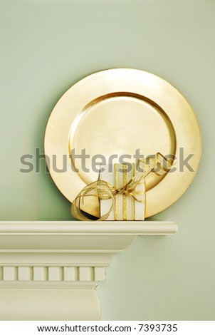 gold plate and gift on a white mantle - stock photo