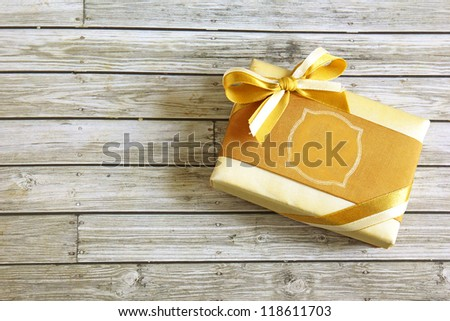 Gold present box on wooden background - stock photo