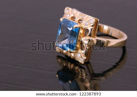 gold ring with big blue gem and smaller diamonds - stock photo