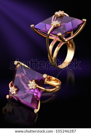 Gold ring with gem and diamonds on dark background - stock photo