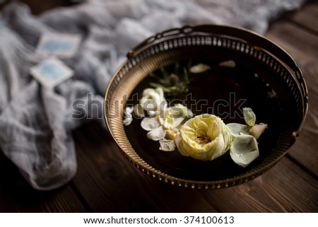 gold rings in flower floating in a copper vase with water on a wooden surface with blue gauze - stock photo
