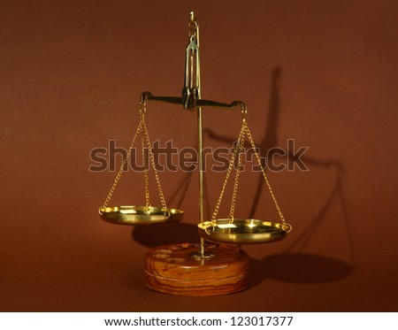 Gold scales of justice on brown background - stock photo