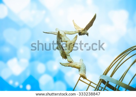 gold Sculpture of a Dove Being Set Free - stock photo