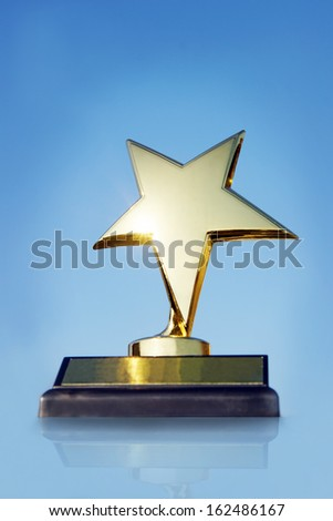 Gold star award on the stand against blue background - stock photo