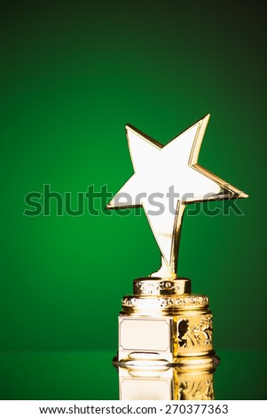 gold star trophy against green background - stock photo