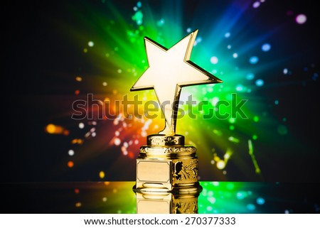 gold star trophy against rainbow sparks background - stock photo