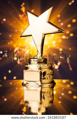 gold star trophy against shiny sparks background - stock photo