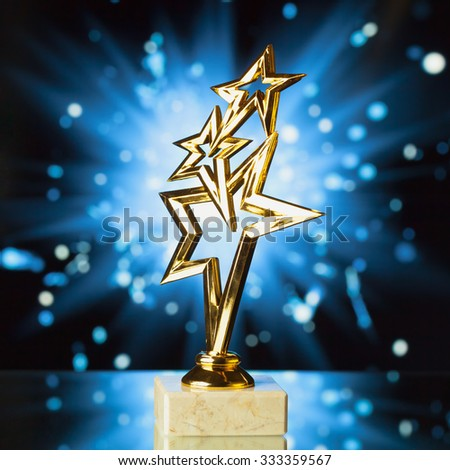 gold stars trophy against blue shiny sparks background - stock photo