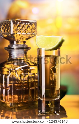 gold tequila and lime on a glass table. - stock photo