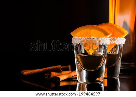 Gold tequila with orange and cinnamon on black reflect background - stock photo