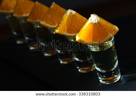 Gold tequila with orange on a dark background - stock photo