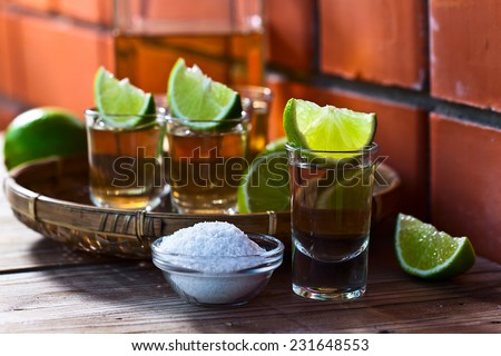 gold tequila with salt and lime on old wooden table. - stock photo