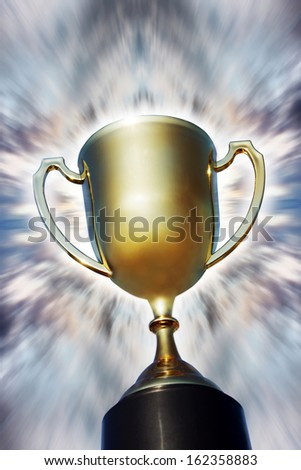 Gold trophy cup against bright background - stock photo