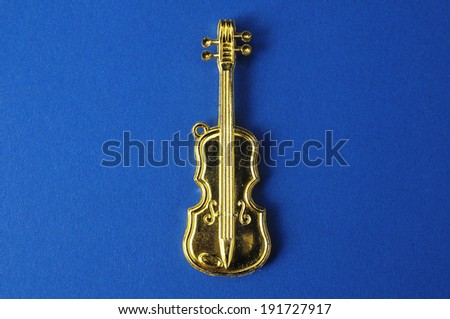 Gold Violin Instrument Figurine on a Colored Background - stock photo