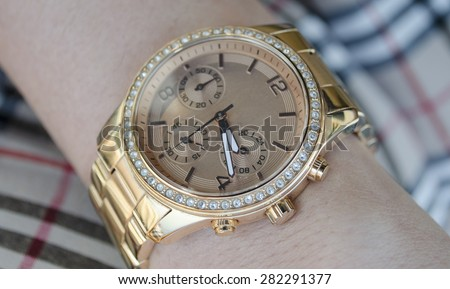 Gold Watches with diamonds on female hand - stock photo