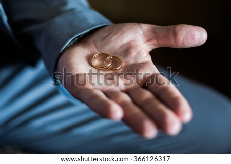 gold wedding ring in a man's hand, the groom holding rings, wedding bands on a dark background, wedding rings hands - stock photo