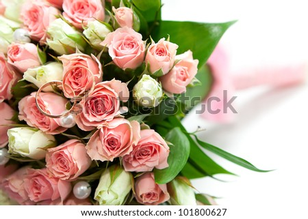Gold wedding rings of the groom and the bride on a bunch of flowers. - stock photo