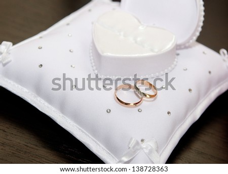 gold wedding rings on the pillow - stock photo