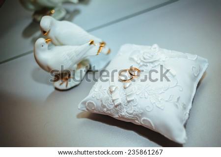 gold wedding rings on the pincushion.  - stock photo