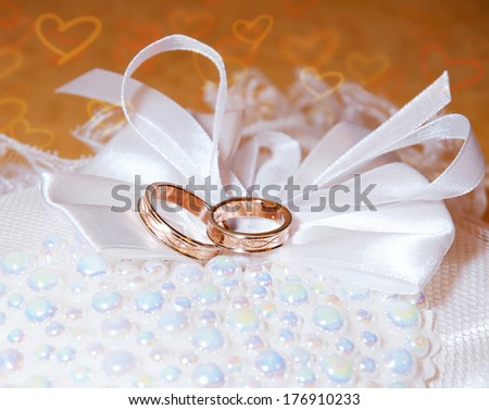 Gold wedding rings on the pincushion. Background with hearts - stock photo