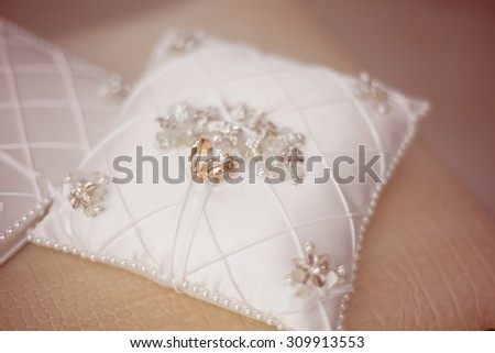 Gold wedding rings on the pincushion, bride and groom decor - stock photo