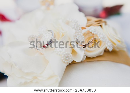 Gold wedding rings on the white and gold pincushion - stock photo