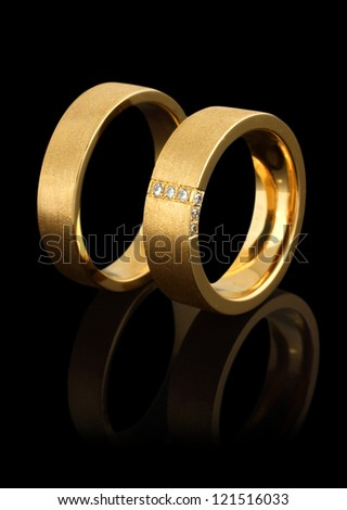 gold wedding rings with diamonds isolated on black background - stock photo