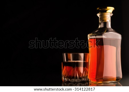 Gold whiskey bottle and glass on dark background. - stock photo