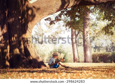 Golden afternoon dream. Boy reading book under big tree - stock photo