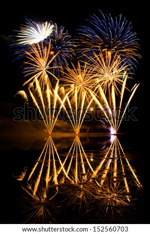 Golden and Blue Fireworks reflected in a murky lake - stock photo