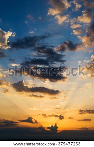 Golden and dark blue vivid sunset sky background with clouds and brightly sunbeams. Colorful sky vertical panorama with orange sun rays. - stock photo
