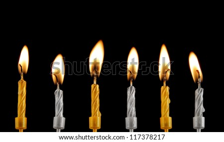 Golden and silver burning candles on black background - stock photo