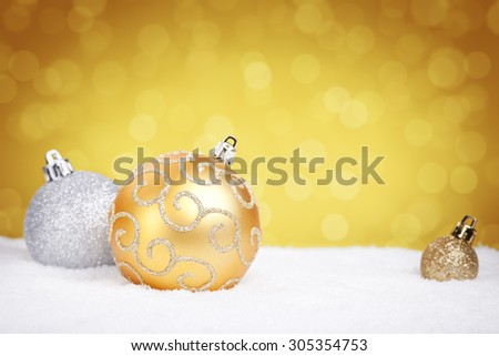Golden and silver Christmas baubles on snow with defocused golden lights in the background. Shallow depth of field. - stock photo