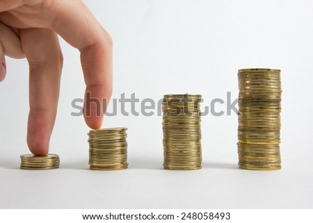 Golden and silver columns of coins isolated on white background - stock photo