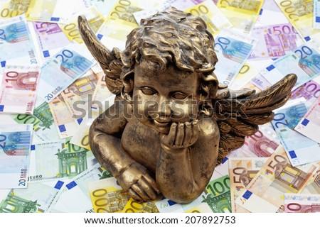 Golden angel sculpture on heap of euro notes - stock photo