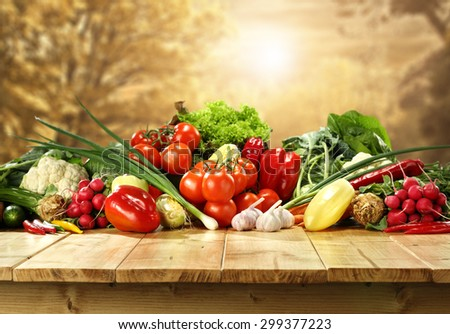 golden autumn background trees and few fresh vegetables on top of table  - stock photo