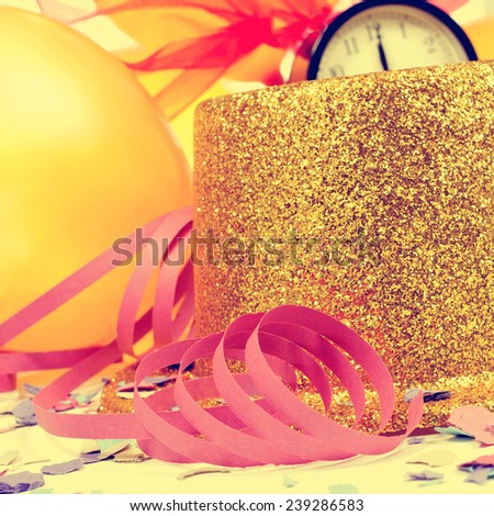 golden balloons, golden top hat, streamers and confetti for the new years party, with a retro effect - stock photo
