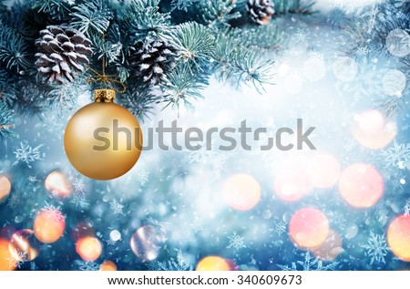 Golden Bauble Hanging Fir Branch With Snowfall - stock photo
